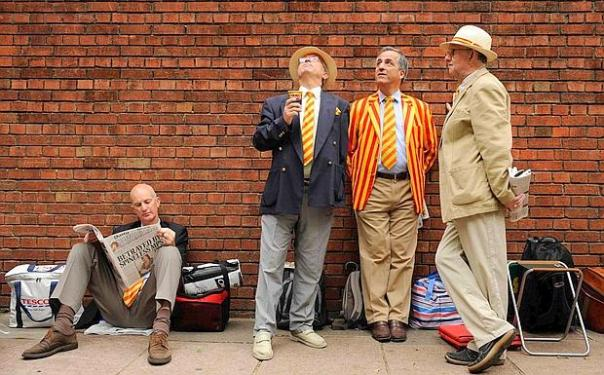 Marylebone Cricket Club members wait in a queue outside the ground before the second Ashes test cricket match between England and Australia at Lord's Cricket Ground